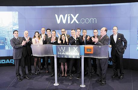 """סמנכ""""ל השיווק של Wix עומר שי (שלישי מימין), המייסדים נדב ואבישי אברהמי (חמישי ושישי), סמנכ""""ל הכספים ליאור שמש, זוהר (חמישי משמאל)והמייסד גיא קפלן (רביעי משמאל) פותחים את המסחר בנאסד""""ק בנובמבר 2013"""