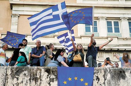 הפגנה באתונה נגד הפרישה מגוש היורו. לו היתה ממשלת יוון מתקפלת בפני הנושים, לא רק שהיא היתה מפרה את התחייבותה הפוליטית, אלא שהיתה עלולה להפר גם התחייבות מוסרית לאזרחיה ולהעמיק את העוני במדינה , צילום: רויטרס