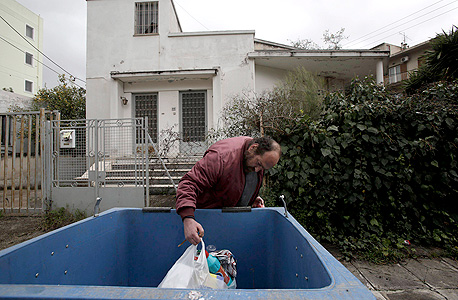מובטל יווני באתונה מחטט בפח זבל