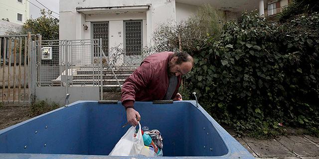 מובטל באתונה מחפש אוכל בפח זבל , צילום: אי פי איי