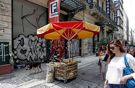 דוכן ריק ומאחוריו חנויות סגורות ביוון, צילום: בלומברג