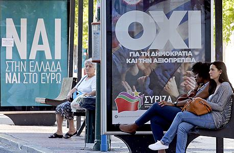 """יוון מפוצלת: תחנת אוטובוס עם שלטי """"כן"""" ו""""לא"""" לקראת המשאל"""