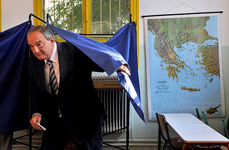 ראש ממשלת יוון לשעבר קוסטס קרמנליס מצביע במשאל עם