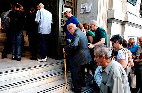 תור של אזרחי יוון ליד אחד מסניפי הבנקים באתונה
