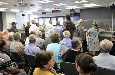 """לקוחות ממתינים בתוך סניף של """"בנק פיראוס"""" באתונה"""