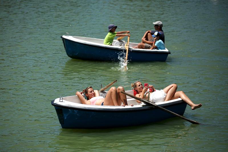 תושבי מדריד משתזפים על בוציות, באגם שבפארק אל רטירו, צילום: גטי אימג