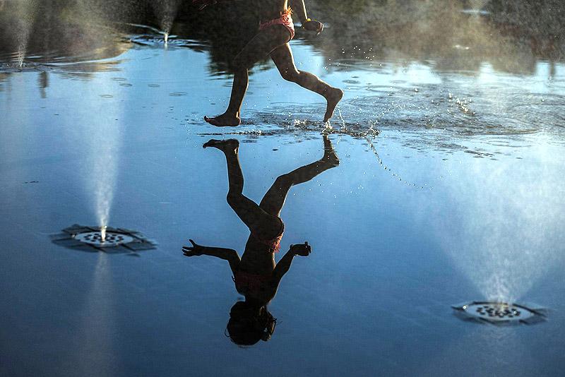 ילד משחק במזרקות רחוב במדריד, צילום: איי פי