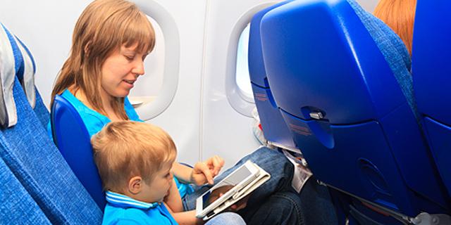 אישה ובנה בטיסה (אילוסטרציה). חברת התעופה הושיבה בנפרד אם וילדיה, צילום: שאטרסטוק