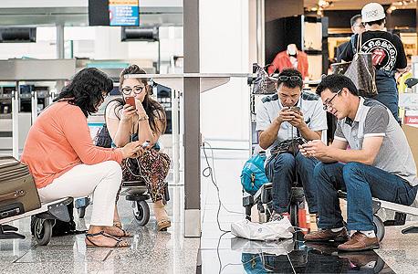 """נוסעים בשדה התעופה בהונג קונג. """"אם אתה נכנס לאתר כמו Expedia מהלפטופ או מהאייפון, ובודק את המחיר באותו מלון באותו תאריך, בנייד יש 30% הנחה, אבל המחיר בנייד צריך דווקא להיות יקר יותר. הם שורפים כסף"""""""