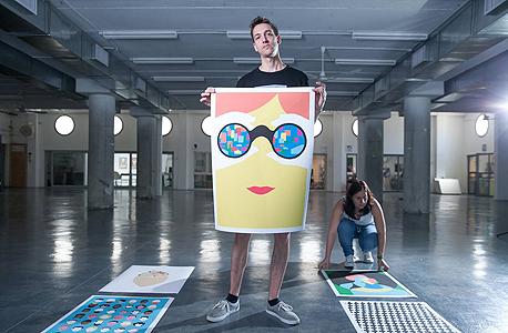 """עמרי כהן עם כרזה מהתערוכה. """"להציף את הנושא עבור נוער מהפריפריה"""""""