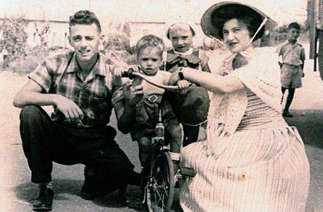 1959. איציק אברכהן, בן 4, עומד במרכז, עם אחיו רענן בן השנתיים והוריו אברהם ורותי, ליד הבית במגדל העמק