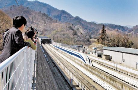 """עיתונאים ביפן צופים בנסיעת מבחן של רכבת מגְלֶב מרחפת שמגיעה למהירות 500 קמ""""ש. ביפן כבר פועלת רכבת מרחפת שנוסעת במהירות 100 קמ""""ש"""