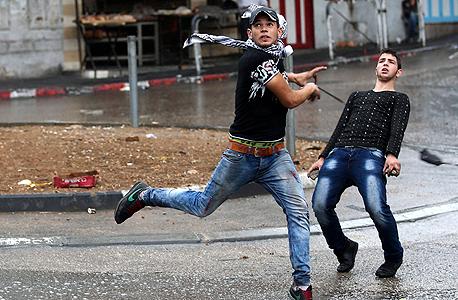 צעירים זורקים אבנים בחברון השוע, צילום: אי פי איי