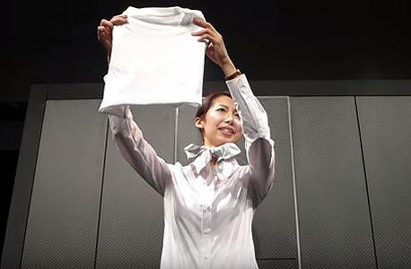 הנציגה מראה את החולצה שקופלה במכונה, צילום: Seven Dreamers Laboratories