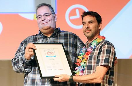 מימין: אמיר אלון מ-E2C, מקבל את הפרס מידי זוהר לבקוביץ', חבר צוות השופטים