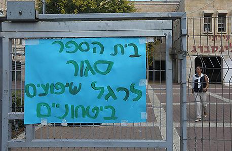 שלט בכניסה לבית הספר במחאה על היעדר אבטחה