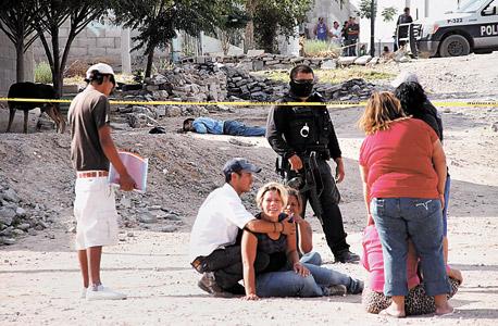 """נשים בוכות על רקע גופות ארבעה גברים שנרצחו בידי חברי כנופייה בחוארז, מקסיקו. """"המידע שלנו סייע להרחיק אנשים כאלה מהרחובות"""" , צילום: אי פי איי"""
