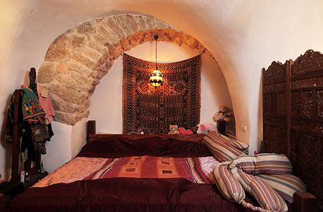 """חדר השינה של בני הזוג. המיטה, ברוחב 2.5 מטרים, תוכננה במיוחד למידותיו של החדר כך שאי אפשר להוציאה ממנו. """"תפרתי לה מצעים וכיסוי מיטה במיוחד"""", אומרת אוריה, צילום: עמית שעל"""