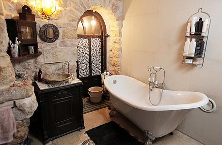 חדר האמבטיה. אמבטיה מחנות יד שנייה בחולון, ארון כיור ששימש בעבר לאחסון גרמופון ומוזאיקה מעשה ידיה של אוריה, צילום: עמית שעל