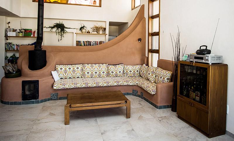 קמין מסה בבית שתכנן האדריכל כפיר וקס בנורית. במקום לבזבז את החום, מנצלים אותו באמצעות תעלה המוסווית בספסל