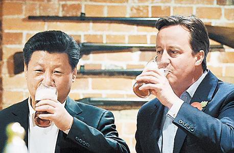 שי לוגם בירה ביחד עם ראש ממשלת בריטניה דיוויד קמרון, באחד ממסעותיו בעולם