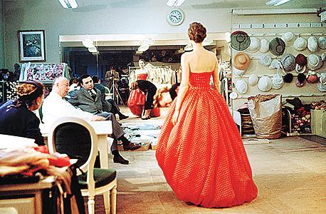 כריסטיאן דיור (משמאל, בחלוק לבן) בוחן שמלת ערב בעיצובו לפני תצוגה (ינואר, 1957)