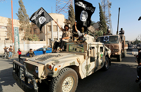 """מצעד צבאי של דאעש במחוז א־רקה בסוריה בשנה שעברה. אלנבלום: """"הפצצות לא יטפלו במקור הבעיה"""" , צילום: רויטרס"""