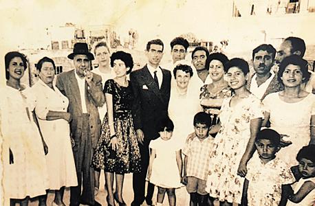 1960. רמי לוי, בן חמש (שני מימין בחולצה פרחונית), עם אמו (בשמלה לבנה מאחוריו) ואביו (מאחוריה), בחתונה משפחתית בירושלים