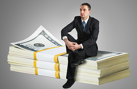 An investor sitting on a pile of cash. Photo: shutterstock