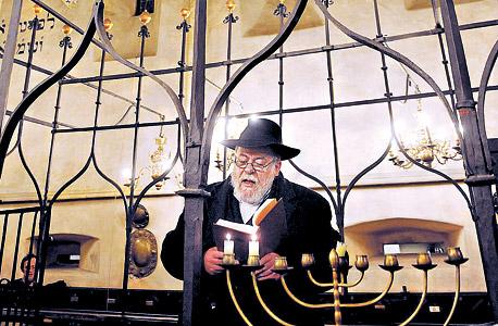 """סידון מדליק נרות חנוכה בבית הכנסת העתיק אלטנוישול. פרש מתפקידו כדי להתמסר לכתיבה, ומ""""סיבות אישיות"""" שצופנות שערורייה קטנה"""