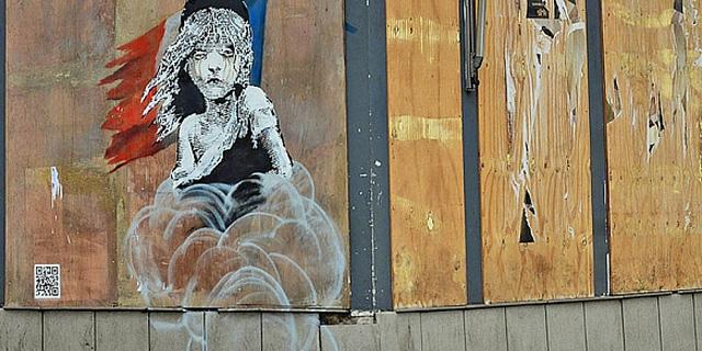 הכתובת על הקיר: בנקסי מוחה על היחס לפליטים על בניין שגרירות צרפת בלונדון
