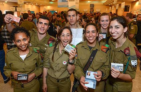 חיילים מציגים את תעודות הזהות שהנפיקו בכנס