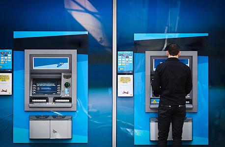 לקוח עומד בכספומט של בנק לאומי, צילום: בלומברג