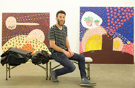 אלעד רוזן על רקע עבודותיו. ילדותיות וצבעוניות מפתה, אבל עם עוקץ