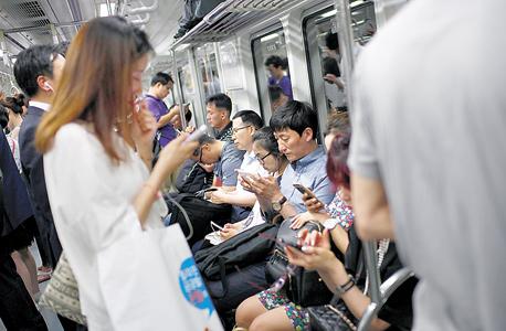 """משתמשי סמארטפון ברכבת בסיאול. """"המשתמשים מדברים כמו מכורים, כמו אנשים שעברו התעללות"""""""