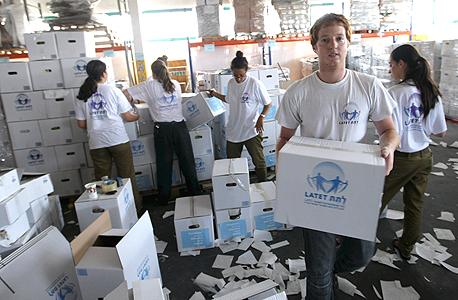 """מתנדבים של """"לתת"""" אורזים מזון חלוקה לנזקקים"""