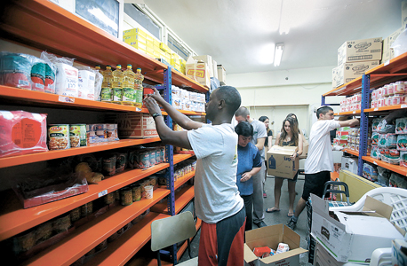 מתנדבים אורזים חבילות סיוע. תרומות אינן אפיק הכנסה עיקרי