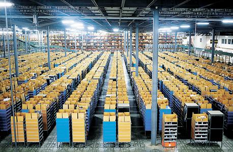 """רובוטים כתומים קטנים של Kiva מזיזים מדפים במחסן של אמזון (מימין), ושל Gilt. גלס: """"מתוך כ־130 מחסנים שיש לאמזון, רק בשמונה עובדים עם רובוטים"""""""