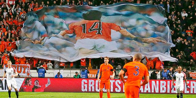 """נבחרת הולנד עם השלט של קרויף באמסטרדם ארנה. """"837 אלף האזרחים באמסטרדם יסכימו שלאצטדיון יקראו על שם קרויף"""", אמר גורם בעיריית אמסטרדם., צילום: איי פי"""