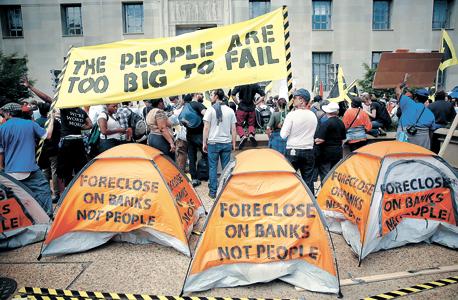 """מפגינים בארה""""ב מוחים נגד פינוי חייבים מבתיהם, בעוד הבנקים זוכים לחילוץ. """"הבנקים אוהבים לתת אשראי לעסקאות נדל""""ן, אבל זה לא אומר שהלוואות כאלו רצויות לשאר החברה"""", צילום: גטי אימג"""