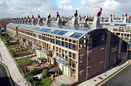 פרויקט BedZED בלונדון. משטחים פוטו-וולטאיים וטורבינות רוח לייצור אנרגיה מתחדשת