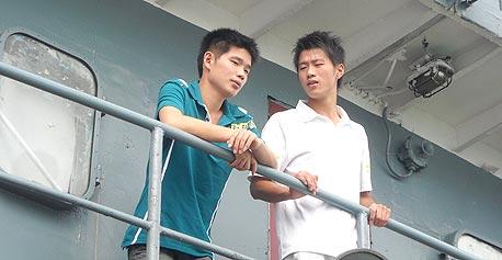 """לין ג'יה (משמאל) עם חבר על המעבורת לפינגטאן. """"עכשיו נוסעים הרבה צעירים, בגלל המשבר"""""""