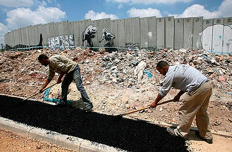 עובדים פלסטינים ליד גדר ההפרדה בגדה (ארכיון), צילום: אי פי אי