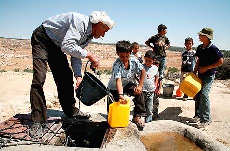 פלסטינים ממלאים מים בכפר יטא, צילום: אי פי אי
