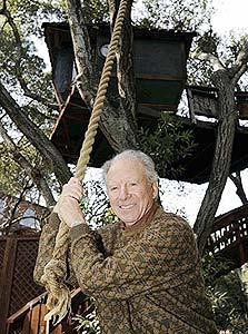 """סטיוארט בראון למרגלות בית העץ המשמש לו כמשרד. """"משחק בכל מה שאני יכול"""""""