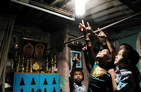 בקבוק שתייה שקוף מלא במים וקצת כלור מאיר בתים של תושבים עניים בפיליפינים