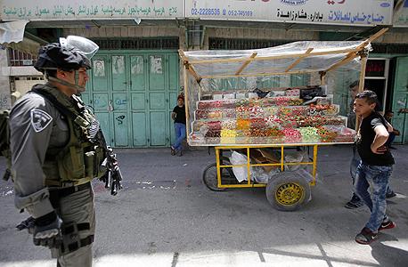 """חייל מג""""ב לצד סוחר ממתקים פלסטיני בחברון, צילום: אי פי איי"""