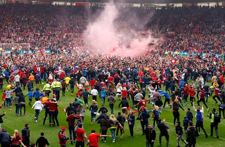 """אוהדי מידלסברו פורצים למגרש. הקבוצה מצפון מזרח אנגליה הבטיחה לעצמה הכנסה של 200 מיליון ליש""""ט - כ-253 מיליון יורו בשנתיים הקרובות. 100 מיליון ליש""""ט לפחות מזכויות שידור בעונה הבאה ו-70 מיליון ליש""""ט ב""""דמי מצנח"""" במקרה של ירידת ליגה, צילום: רויטרס"""