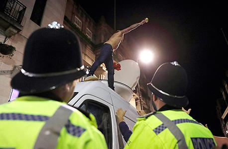 שוטרים משגיחים על אוהד. הפשעים האמיתיים מתרחשים בחדרי הישבות, צילום: רויטרס