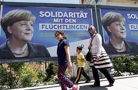פוסטר של הקנצלרית מרקל הקוראת לשילוב פליטים, צילום: אי פי איי